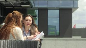 Two businesswomen talking and looking through papers in outdoor cafe stock footage