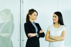 Two businesswomen talking in an office with reflection Royalty Free Stock Photography