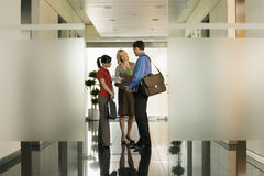 Two businesswomen talking to businessman in office corridor, smiling, side view Royalty Free Stock Photos
