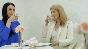 Two businesswomen talks and drinks coffee in cafe. Two adult women sits in cafe and communicates. Pretty blonde and brunette drinks coffee and enjoys the stock footage