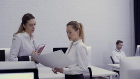 Two businesswomen discusses new project in the office. Two businesswomen talks in the office. Attractive women discusses some working issues and looks at the stock video footage