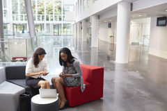 Two Businesswomen Using Mobile Phones In Lobby Of Office Stock Photo