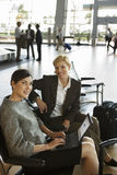 Two businesswomen waiting in airport departure lounge, woman using laptop, smiling, side view, portrait Stock Photos