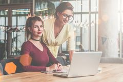 Two businesswomen working together. On desk is laptop. Woman is standing near table, girl is sitting next to her. Teamwork.Girls blogging,working,learning Stock Image