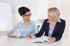 Two businesswomen working together at desk at office. Teamwork at office with two business women Stock Photography
