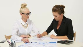 Two businesswomen working together at desk office. Two businesswomen working together at desk at office stock video