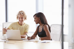 Two Businesswomen Working Together On Laptop In Boardroom Stock Images