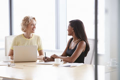 Two Businesswomen Working Together On Laptop In Boardroom Royalty Free Stock Photo