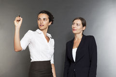 Two businesswomen write on a virtual screen Royalty Free Stock Photos
