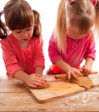 Two busy little girls kneading and rolling Royalty Free Stock Photo