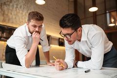 Two busy pensive businessmen working on a business plan Royalty Free Stock Photography
