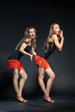 Two cabaret dancers in bright costumes over dark Royalty Free Stock Photos
