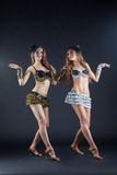 Two cabaret dancers in bright costumes over dark Stock Photo