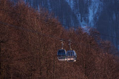 Two cabins of gondola at sunset. On the background of forests and mountains Stock Photography
