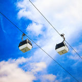 Two cable car on a partly cloudy sky background Royalty Free Stock Image
