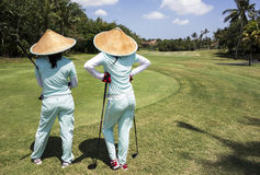 Two Caddies On Bali Golf Course. BALI, INDONESIA - NOVEMBER 8, 2012: Two caddies with straw hats on a golf course near Tabanan watch as their players hit on the Stock Image