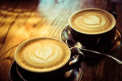 Two cafe lattes on a wooden table stock photo