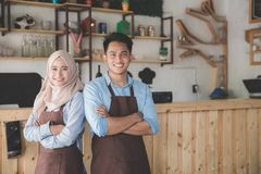 Two cafe owner standing with crossed arms. Successful two coffee shop owner standing with crossed arms with partner Stock Photos