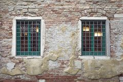 Two caged windows. On ancient brick wall in Venice Royalty Free Stock Photos