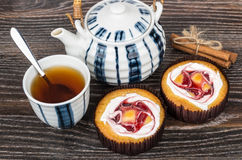 Two cakes, cup of tea, cinnamon sticks and teapot Royalty Free Stock Images