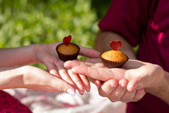 Two cakes on male and female hands Stock Photography