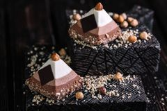 Two cakes three chocolate mousse in the shape of a pyramid. On wood background Stock Photos