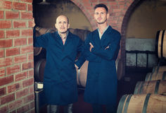 Two calm men in uniforms standing in cellar with wine woods Stock Photography