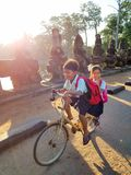 Two cambodian children in uniforms. Siem Reap, Cambodia - DECEMBER 29, 2017: Two cambodian children in uniforms going to school by bike Stock Images