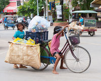 Two Cambodian children at work. SIEM REAP, CAMBODIA - JUNE 28, 2014: Two local unidentified girls of school age pose for camera carrying large bags with trash on Stock Photography