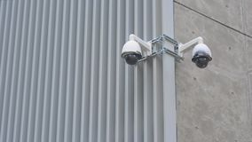Two cameras fixed on a building in a white case dome metal concrete. background technology security cameras. Monitoring people controll private lives, digital stock footage