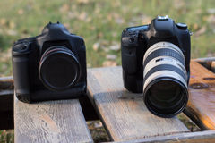Two cameras with lenses lie on a sun lounger . Stock Images