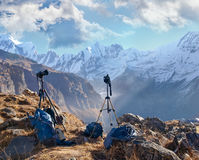 Two cameras on tripods against of mountain range and gorge. Two cameras on tripods on the background of a mountain range with peaks covered with glaciers, deep Royalty Free Stock Photo