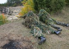Two camouflage hunters or soldiers hiding in bushes in camouflage. Autumn background. Sniper with rifle Royalty Free Stock Photo