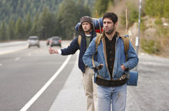 Two camping buddies hitchhiking. On a mountain road Royalty Free Stock Image