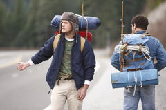 Two camping buddies hitchhiking. On a mountain road Royalty Free Stock Images