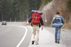Two camping buddies hitchhiking. On a mountain road Stock Photos