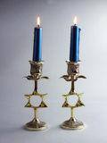 Two candle holders with burning candles. Two candles burning, with decorative metal candle holders, with Star of David Stock Image