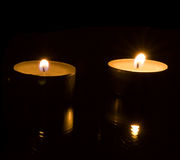 Two candles. On black background Stock Photography