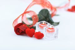 Two candles and a beautiful rose on a white background Royalty Free Stock Photos