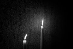 Two candles. A black and white shot of two candles at different height shot against a textured wall Royalty Free Stock Image