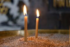Two candles burn in the Orthodox Church before the icons. Two candles burn in the Orthodox Church before the icon closeup photo Royalty Free Stock Photos