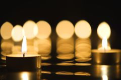 Two candles burning in darkness. Beautiful candlelight and reflection of burning candles in the background Stock Image