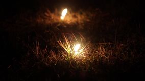 Two candles burning down in the grass. Two candles burning down in the dry grass stock video