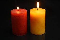 Two candles. Two burning candles red and yellow. one with small flame, one with larger stock photography