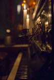 Two candles in candlesticks attached to the wall of black piano royalty free stock photo