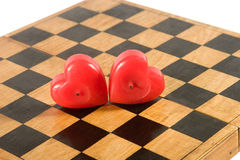 Two candles on a chessboard. Two heart-shaped red candles on an old chessboard Stock Photo