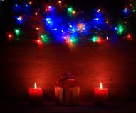Two candles and Christmas gift on holiday background. Royalty Free Stock Photos