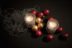 Two candles with christmas-tree decorations Stock Photo