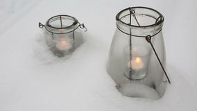 Two candles in glasses in the snow. Two burning candles in glasses in the snow stock video footage