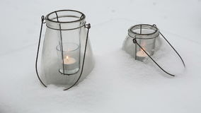 Two candles in glasses in the snow. Two burning candles in glasses in the snow stock video